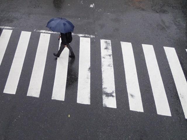 雨の日に傘をさして歩く男性
